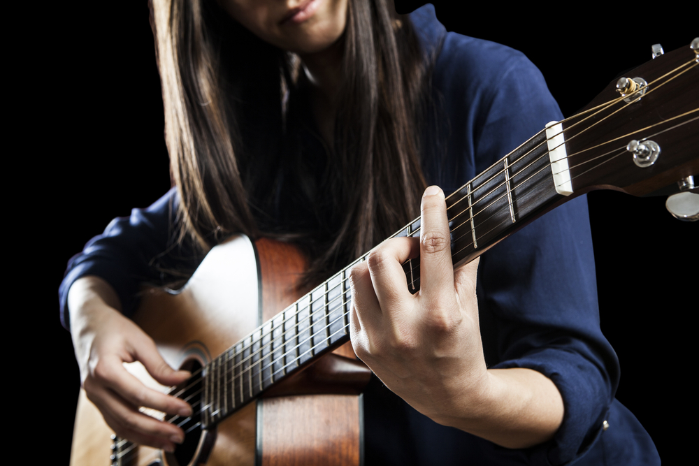 Female Singer Playing An Acoustic Guitar